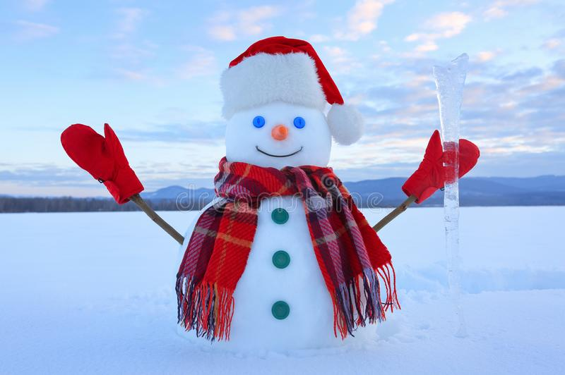 The snowman in plaid scarf, red hat, gloves. Amazing sunrise enlighten the sky. Nice landscape with the mountains. Winter day. stock photo