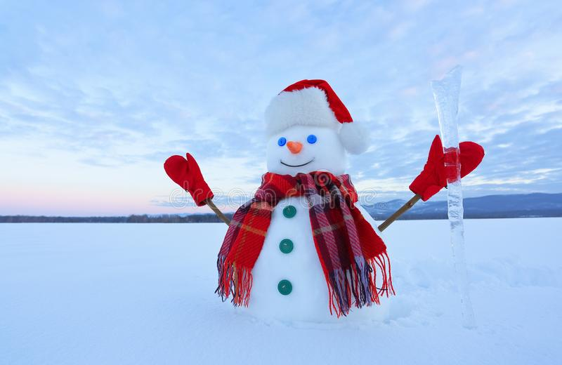 The snowman in plaid scarf, red hat, gloves. Amazing sunrise enlighten the sky. Nice landscape with the mountains. Winter day. royalty free stock photo