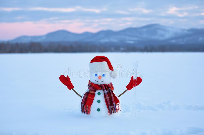 The snowman in plaid scarf, red hat, gloves. Amazing sunrise enlighten the sky. Nice landscape with the mountains. Winter day. stock image