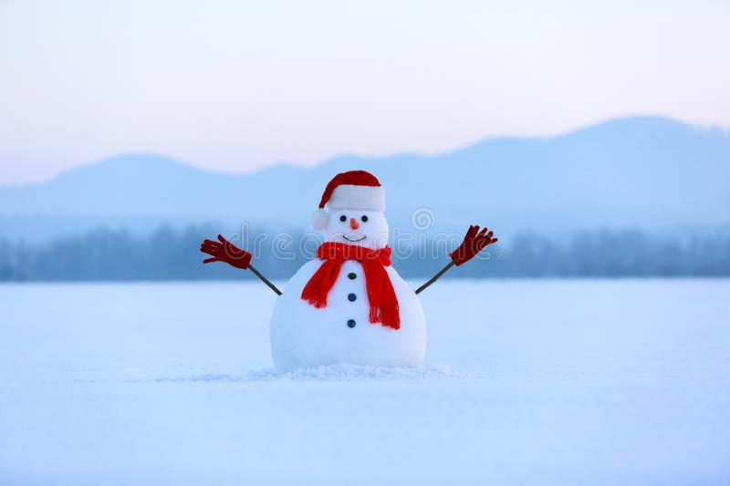 Snowman in red hat and scarf. Christmas scenery. High mountains at the background. Ground covered by snow. royalty free stock photo