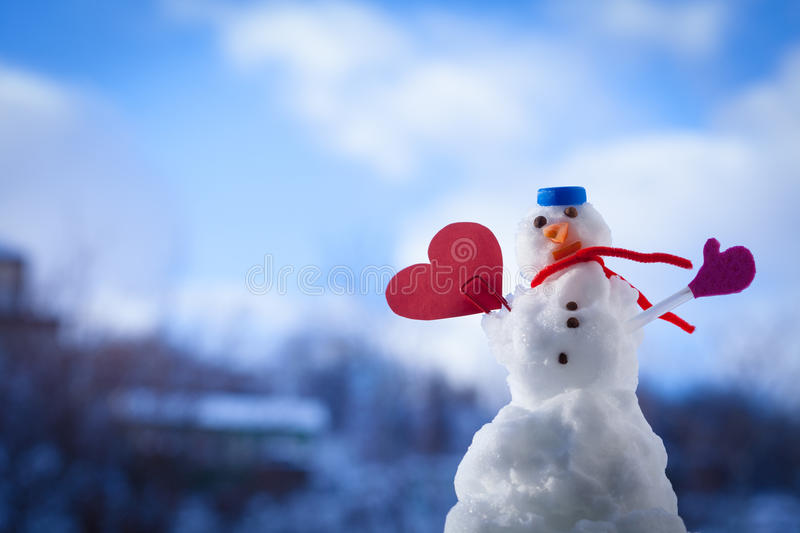 Snowman red heart love symbol outdoor. Winter. Little happy christmas snowman in blue top as hat red scarf and with clip red heart love symbol outdoor. Winter royalty free stock photography