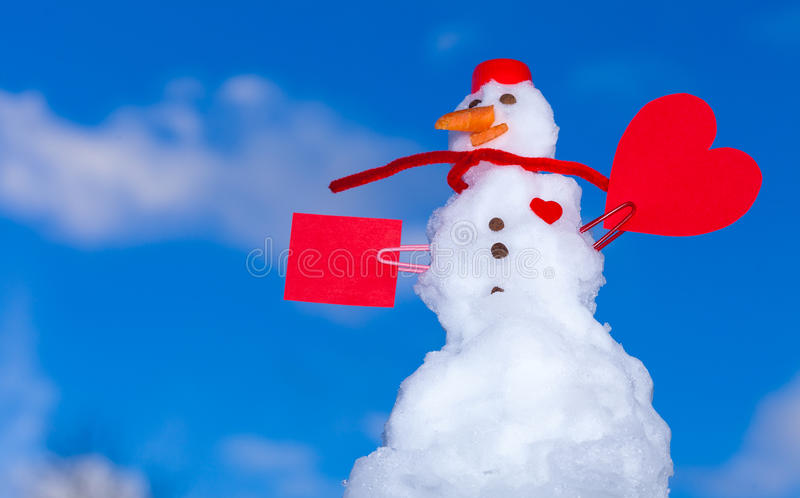 Snowman red heart love symbol outdoor. Winter. Little happy christmas snowman in red scarf and with clip heart love symbol valentine paper card text message stock photography