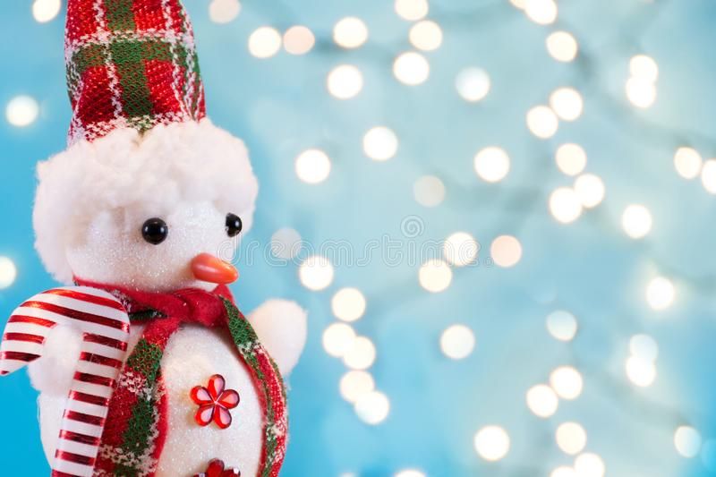 Snowman retro toy with winter scarf and hat and Christmas orb lights royalty free stock images