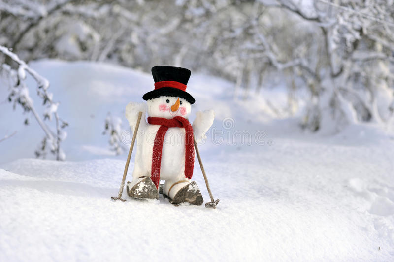 Snowman skiing in winter landscape stock photos