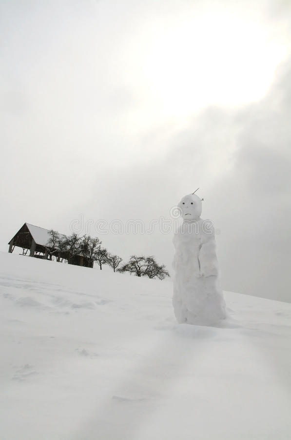 Snowman in the snowy slope stock photo