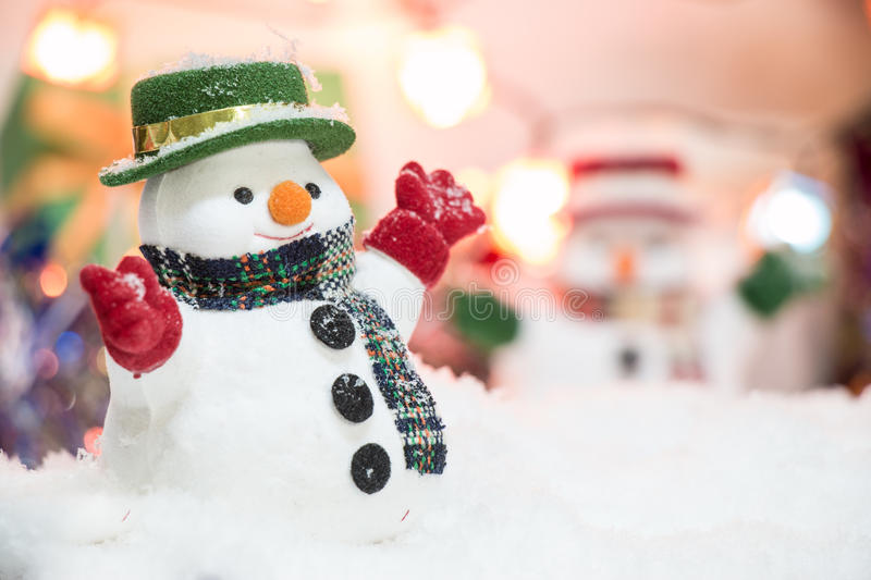 Snowman stand among pile of snow at silent night with a light bulb,Merry christmas and new year night. Snowman stand among pile of snow at silent night with a stock photos