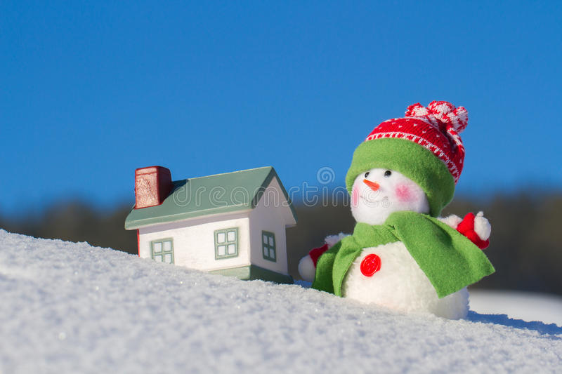 The snowman stands next to the house on a snow slope. Blue sky. Winter background. royalty free stock photos