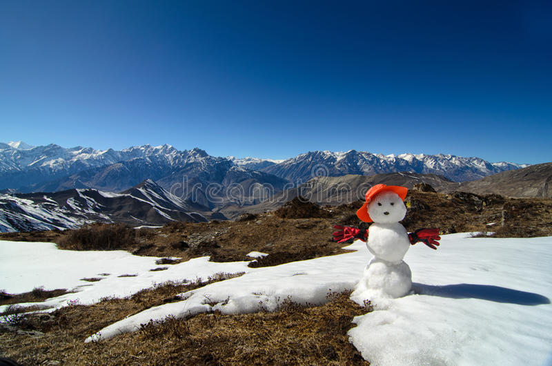 Snowman on top of a mountain with mountain range at the background royalty free stock photo