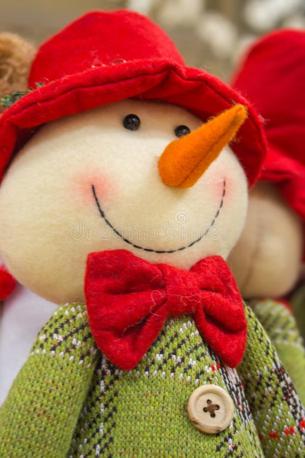Snowman toy with red santa hat and carrot nose. Cute smiling snowman doll. Merry Christmas card concept. Winter fun and joy. stock images