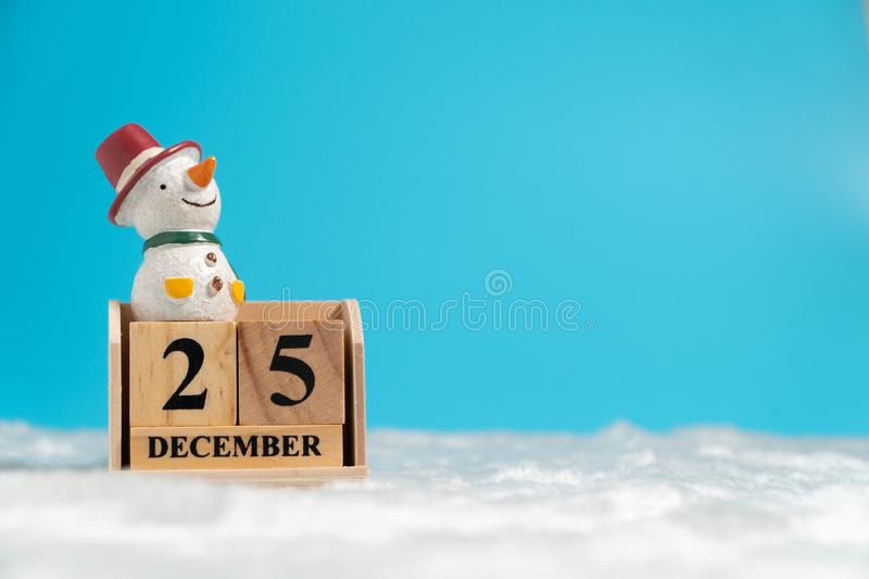 Snowman wearing a red hat sitting on wooden block calendar set on the Christmas date 25 december on white wool and blue background royalty free stock images