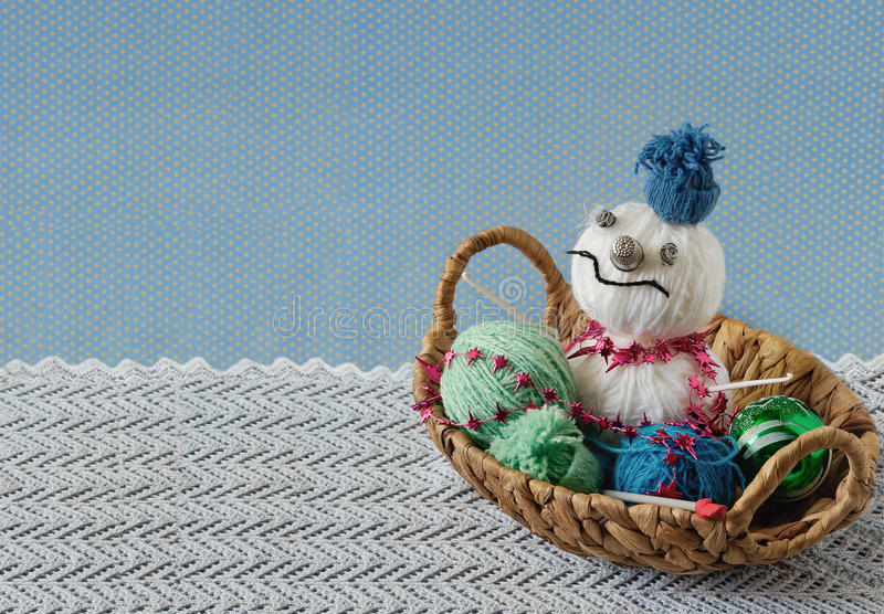 Snowman from yarn hanks in a basket. Skeins of yarn and Christmas balls in a basket royalty free stock images