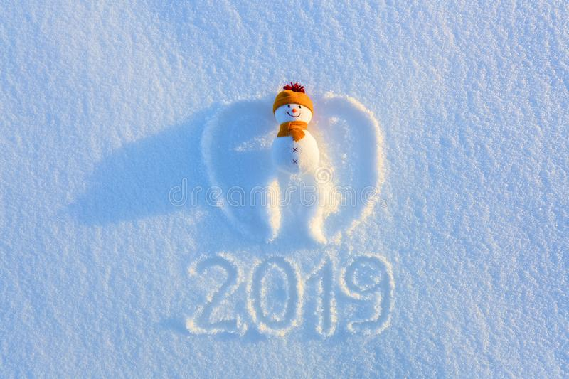 Snowman in yellow hat and scarf on the snow with drawn wings in yellow hat and scarf is laying on the snow. Writing 2019. royalty free stock photography