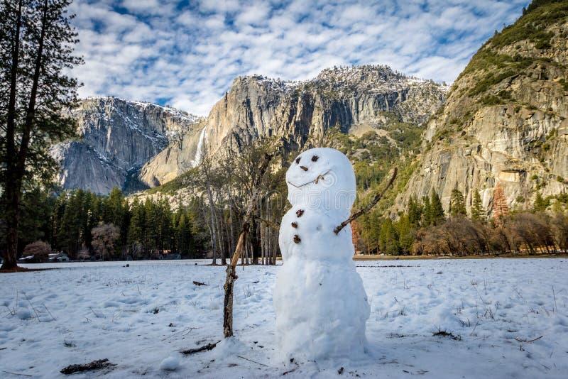 Snowman at Yosemite Valley during winter with Upper Yosemite Falls on background - Yosemite National Park, California, USA stock image