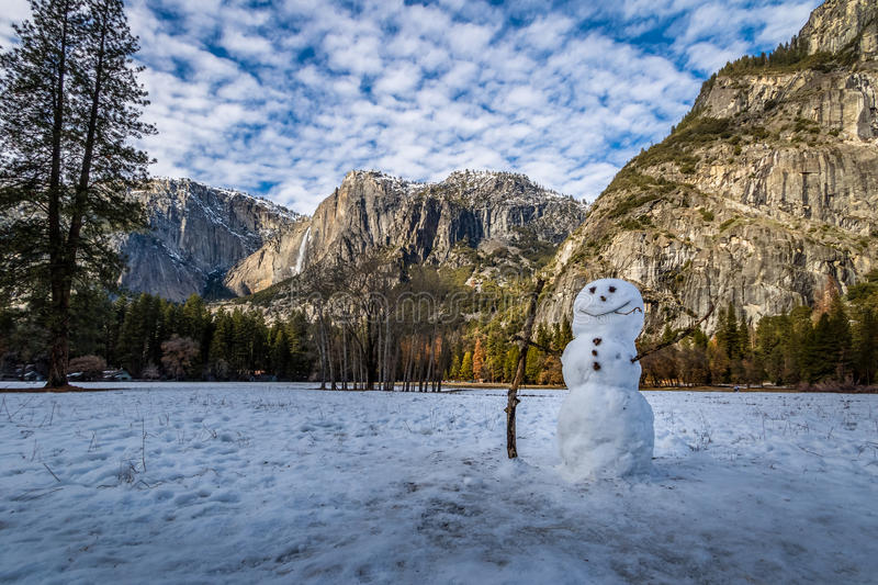 Snowman at Yosemite Valley during winter with Upper Yosemite Falls on background - Yosemite National Park, California, USA royalty free stock images