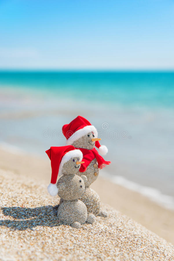 Snowmans couple at sea beach in christmas hat. New years holiday. Smiley sandy snowmans couple at sea beach in christmas hat. New years holiday in hot countries stock images