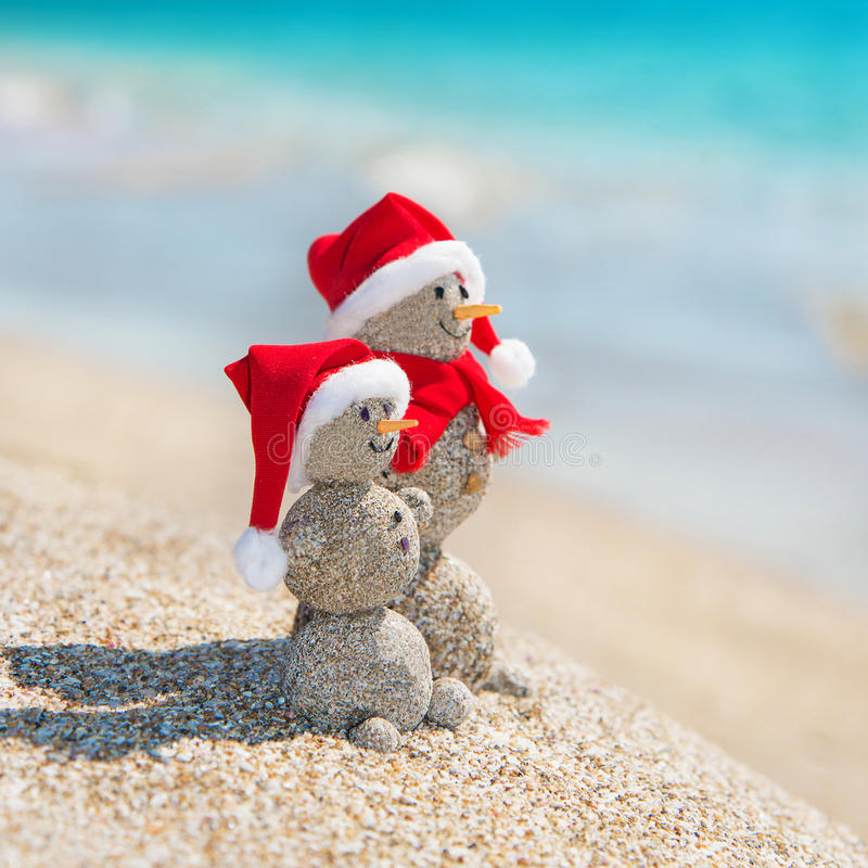 Snowmans couple at sea beach in christmas hat. New years holiday. Smiley sandy snowmans couple at sea beach in christmas hat. New years holiday in hot countries royalty free stock photo