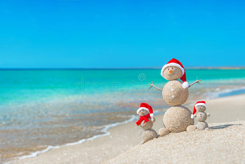 Snowmans family at sea beach in santa hat. Snowmans family at sea beach in santa hats. New years and christmas holiday in hot countries concept royalty free stock photography