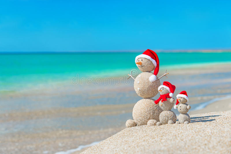 Snowmans family at sea beach in santa hat. Snowmans family at sea beach in santa hats. New years and christmas holiday in hot countries concept stock image