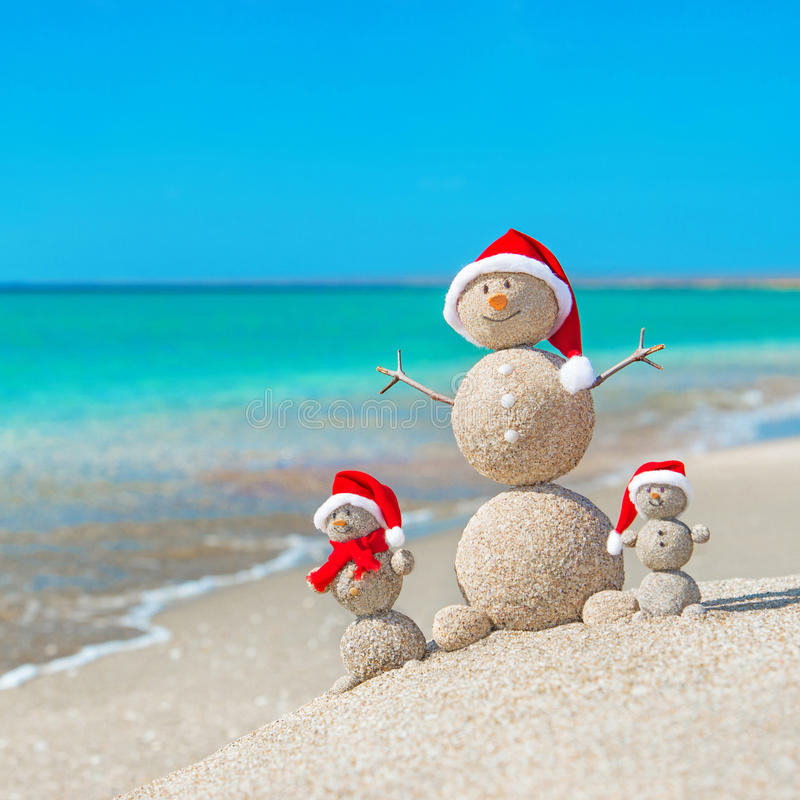 Snowmans family at sea beach in santa hat. Snowmans family at sea beach in santa hats. New years and christmas holiday in hot countries concept stock images