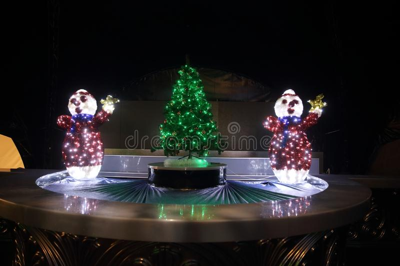 Snowmen and Christmas tree in the city street on Christmas night. Holiday concept stock photos