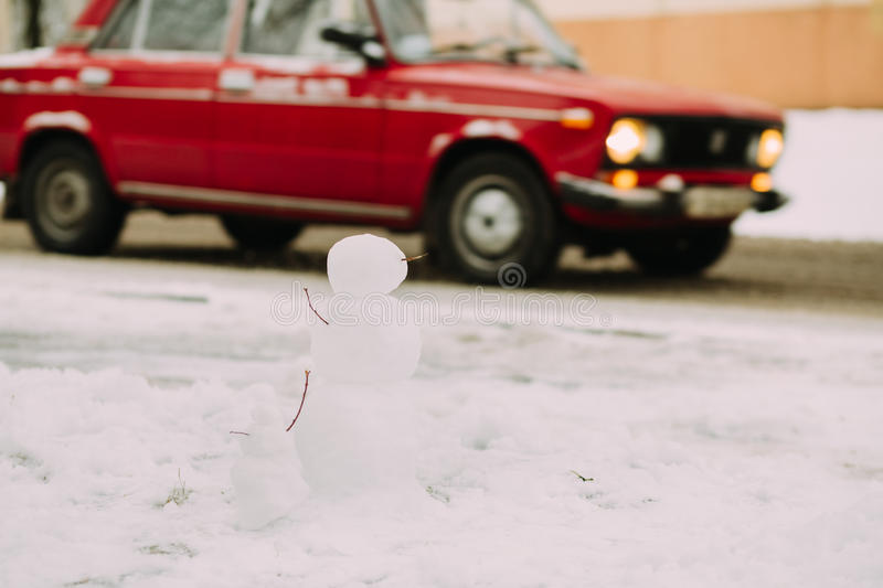 Snowmen at the road with red car. Two snowmen and red car at background in winter royalty free stock photos