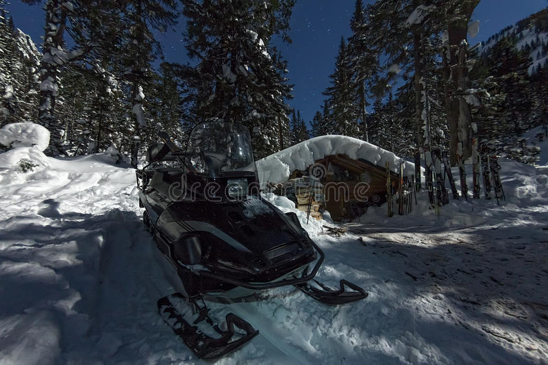Snowmobile from house chalets in winter forest with snow in light moon and starry sky.  stock image