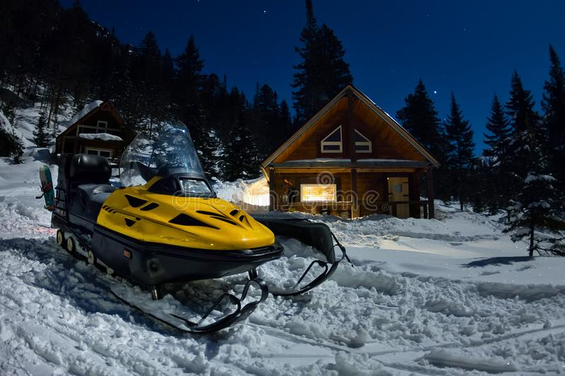Snowmobile from house chalets in winter forest with snow in light moon and starry sky.  stock photography
