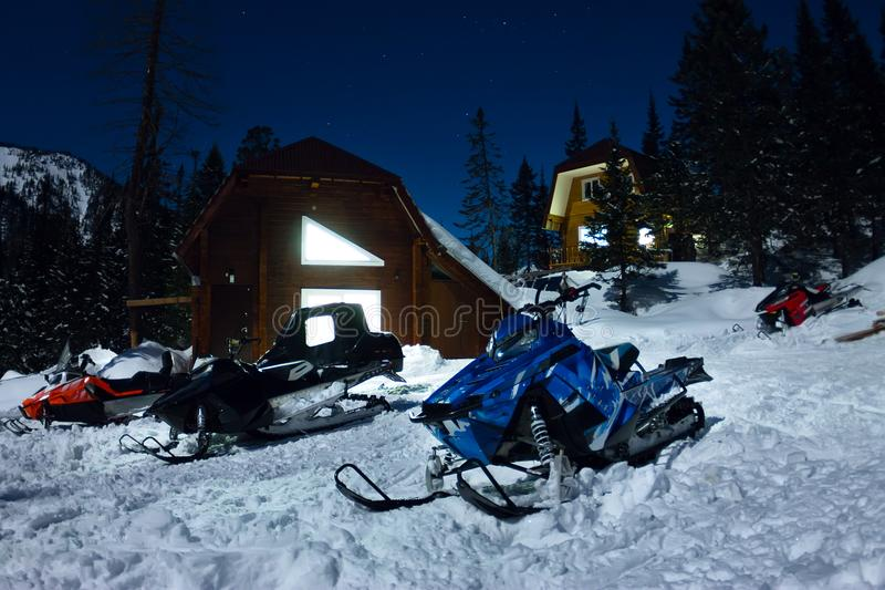 Snowmobile from house chalets in winter forest with snow in light moon and starry sky.  royalty free stock image