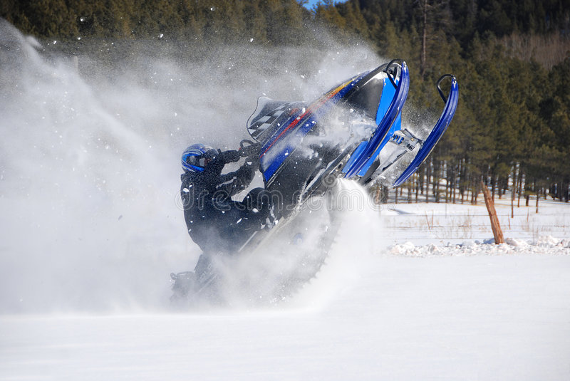 Snowmobile Rider Jumping. A snowmobile rider is jumping with snow spraying everywhere stock photo