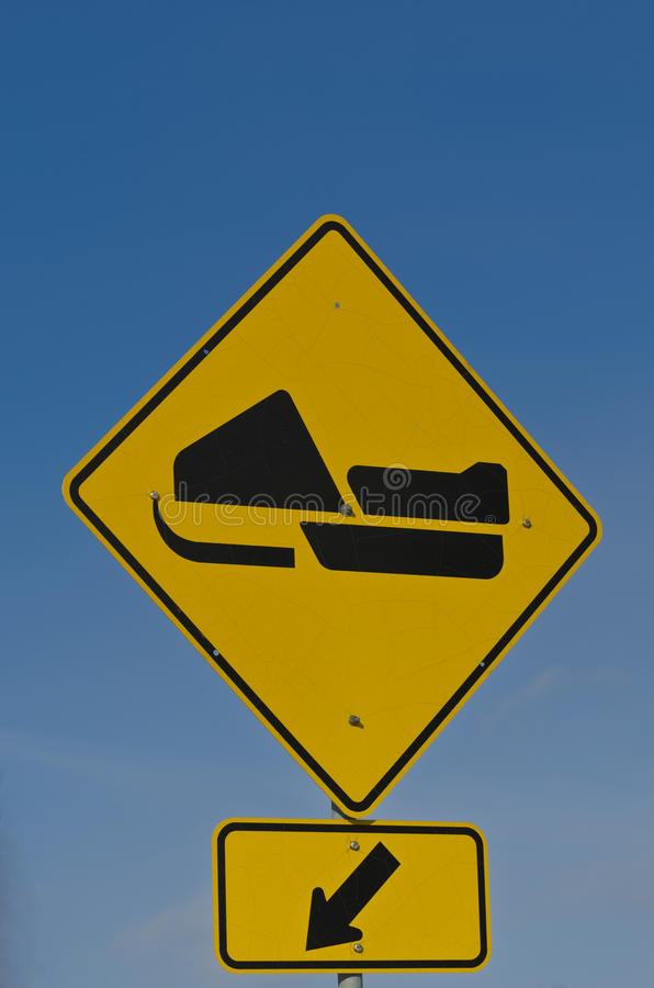 Snowmobile Road Crossing Sign. In yellow and black with deep blue sky background stock photo
