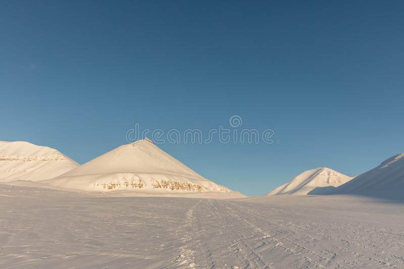 Snowmobile tracks in arctic winter landscape with snow covered mountains on Svalbard, Norway royalty free stock images