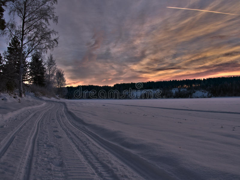 Snowmobile tracks in a winter landscape royalty free stock photography