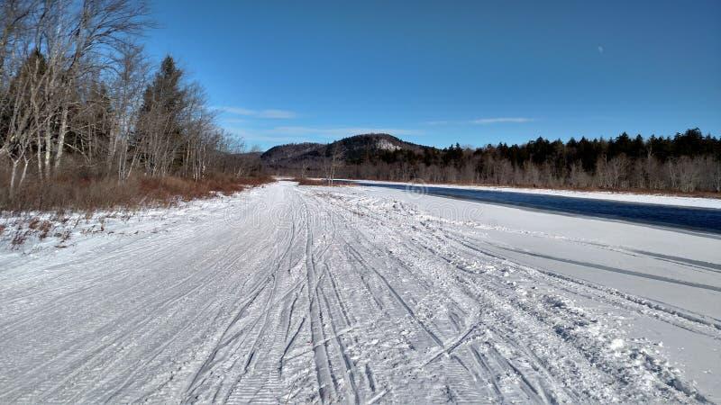 Snowmobile trail through river valley stock photo