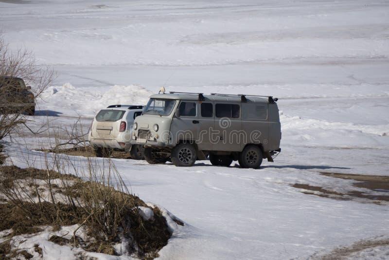 Snowmobile z przyczepą jedzie na zamarzniętym jeziorze przy zmierzchem Sposoby transport w zimie fotografia stock