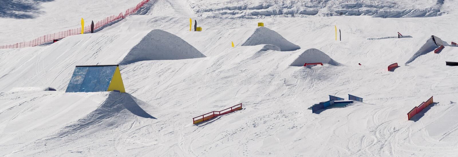 Snowpark with ski ramps, kickers, rails. For big air jumping, jibbing, etc. for freestyle snowboarders and skiers royalty free stock image