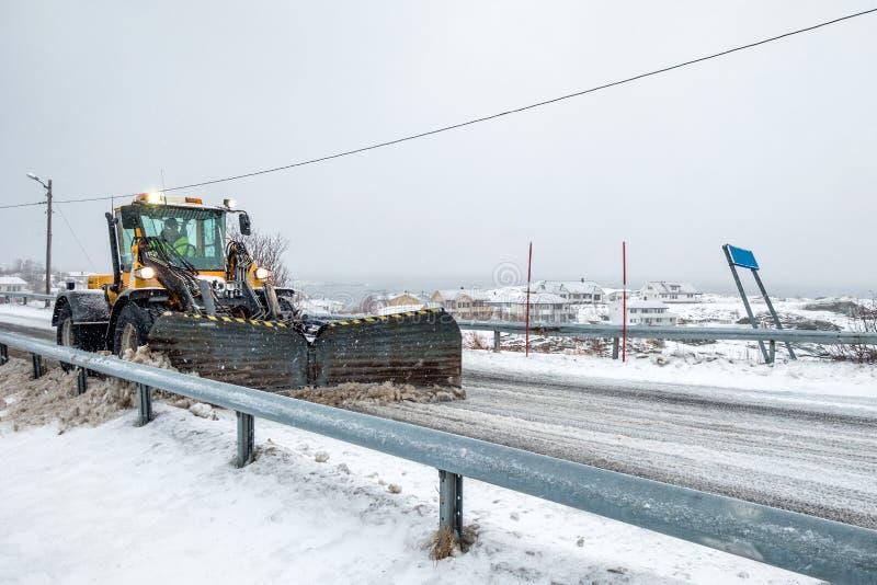 Snowplough amarillo que ara en el camino nevoso imagen de archivo