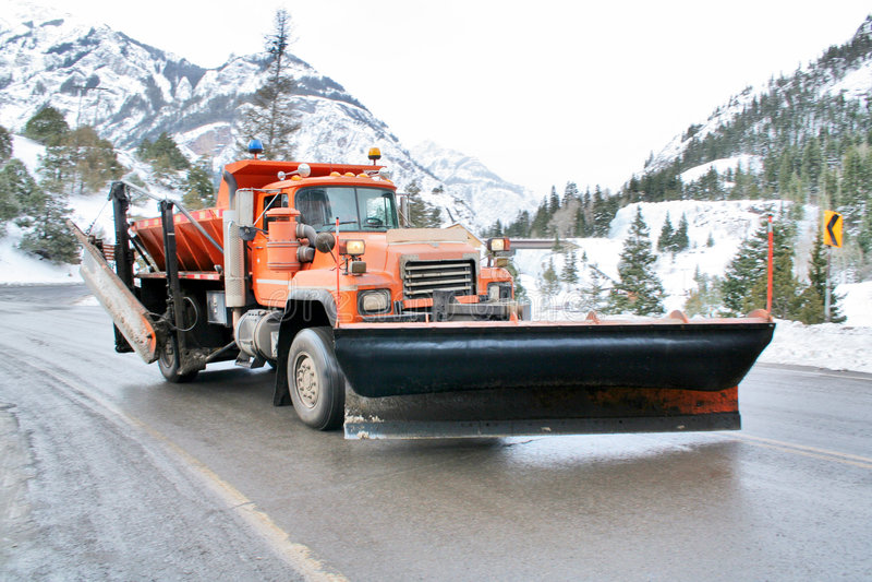 Snowplow. On wet mountain highway stock photos