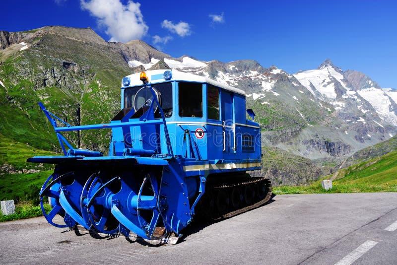 Snowplow azul em um estacionamento na estrada alpina alta de Grossglockner nas horas de verão imagens de stock royalty free