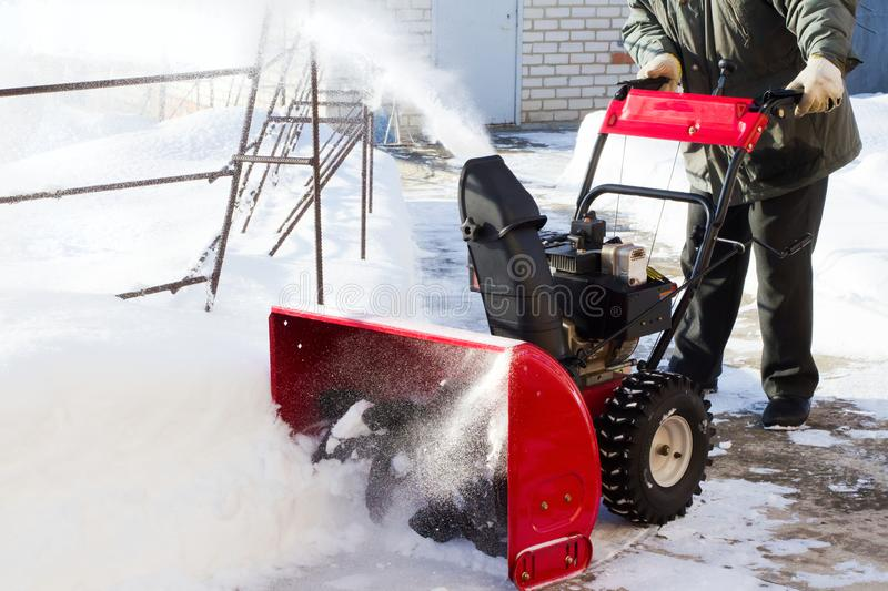 A snowplow clears the road to the plot stock photo