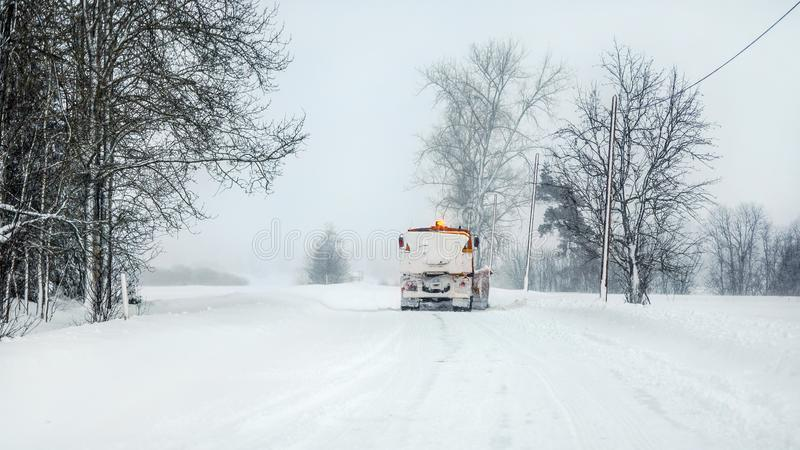 Snowplow highway maintenenace truck cleaning road completely white from snow in winter, dangerous driving conditions, view from stock image