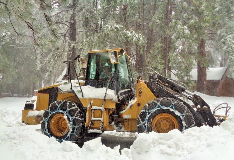 Snowplow que cancela uma estrada residencial em uma tempestade de neve pesada imagem de stock