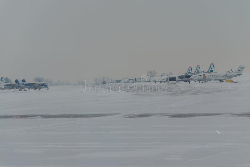 Snowplow que remove a neve das pistas de decolagem e das estradas no aeroporto durante a tempestade da neve, vista através da jan imagens de stock