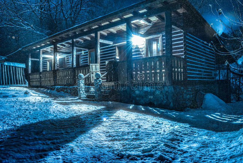 It snows over chalet by night. HDR royalty free stock photos