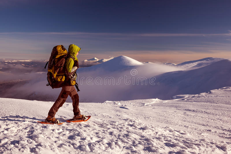 snowshoeing在冬天山的妇女 免版税库存图片
