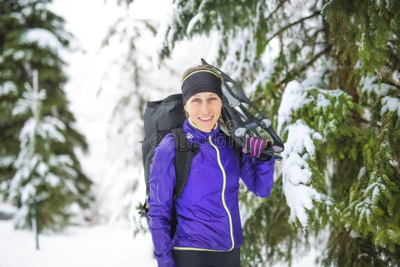 snowshoeing的冬天 拿着雪靴外面在雪的年轻outdoorswoman远足者 库存照片