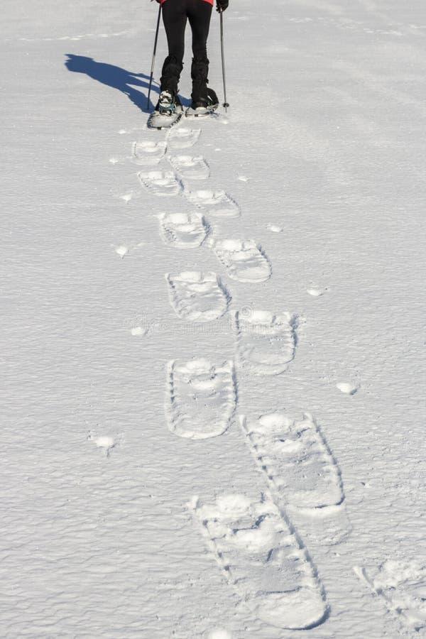 Snowshoeing - vrouwentrekking in de winterbergen royalty-vrije stock afbeelding