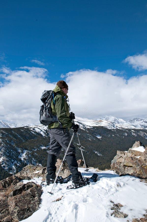Snowshoer on a summit stock photo