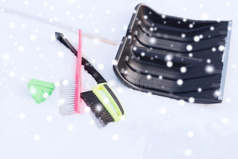 Snowshowel negro con la manija de madera en pila de la nieve fotografía de archivo