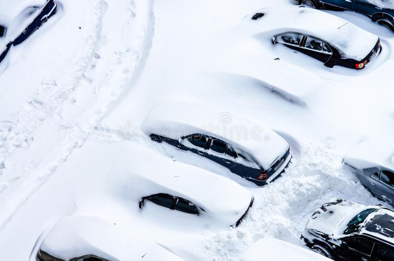 After a snowstorm, cars in the parking lot are covered with a th stock image