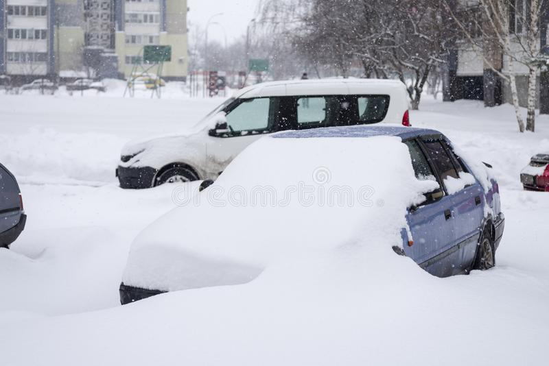 A snowstorm in the city. Cars covered with snow stock photos